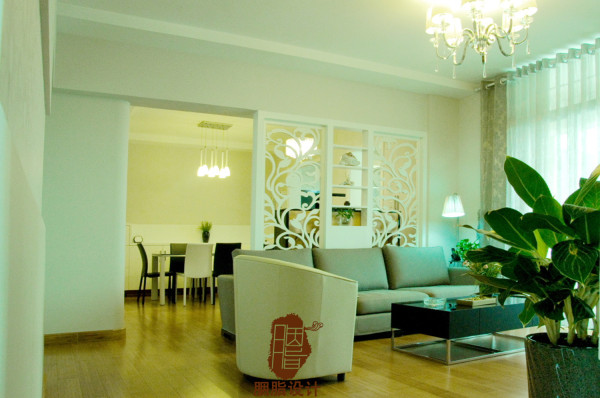 通过白色的缕花屏风设计使得客厅与餐厅之间有种