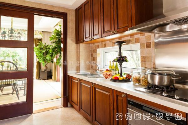 【厨房】厨房选用整体橱柜来打造,实木的材质透露出美式乡村的气韵,在装饰上搭配仿古砖以及仿木纹色的实木门扇,操作台面作适当的色彩调和,美观与实用兼具。