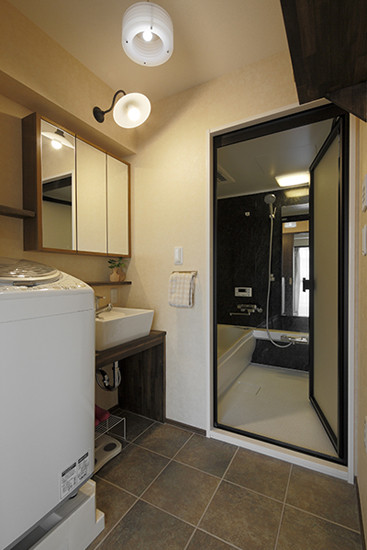 白色的洗脸盆,搭配银色金属水龙头,简单大方。长方形的镜柜,不仅可以供主人整理穿戴,还起到了收纳作用。白色壁灯,搭配黑色金属支架,复古风格浓厚。