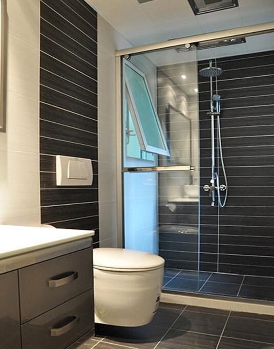 洗手间以永恒流行色——黑白灰为 主色调,黑色的瓷砖横向开槽增视觉上增加了空间感,同时装点了枯燥的马桶,强化了淋浴区。