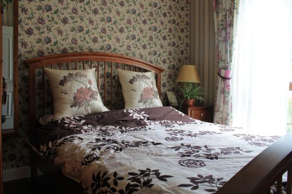 对于卧室床品的选择,设计师选择了素雅的白、紫相间的棉麻制品,大朵牡丹的窗帘和小碎花的壁纸也是为了映照卧室的闲适。在经过适当的搭配之后,简单的饰品共同构成了乡村气息浓厚的别墅空间。