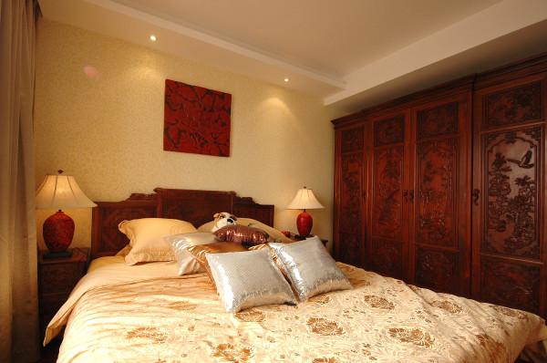 主卧的装饰风格在众多房间内显得极为别致,中式情结浓重却又很摩登。实木雕花立柜带来平和沉静之感,浮雕的图案均为传统喜庆吉祥的题材,床单上大朵大朵的花卉图案绽放出点点富贵。