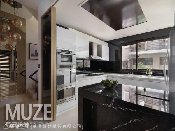 设计师构筑一处美型且机能充足的餐厨空间,并运用简洁线条与黑白的色调,让立面干净利落;古铜色的门框搭配黑玻作为拉门设计,更可有效区隔料理时的油烟逸散。