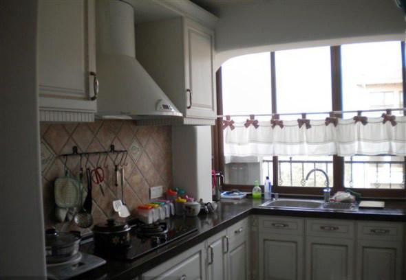 温馨的土黄色小方砖,拼贴出厨房的墙面,对于暖意融融的厨房而言,是最合适不过的色彩。白色的橱柜延续了黄、白、蓝的地中海经典配色。