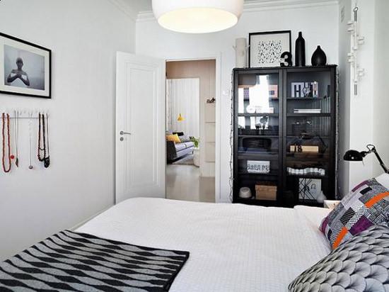 卧室依然简洁,没有过多的摆设,在黑色橱柜的冷硬下,抱枕的斑斓色调让黑白之中有了温度,瑞典家居特有的雅致摩登改变了纯北欧风格的枯燥寒冷,带来了淡淡的舒适。