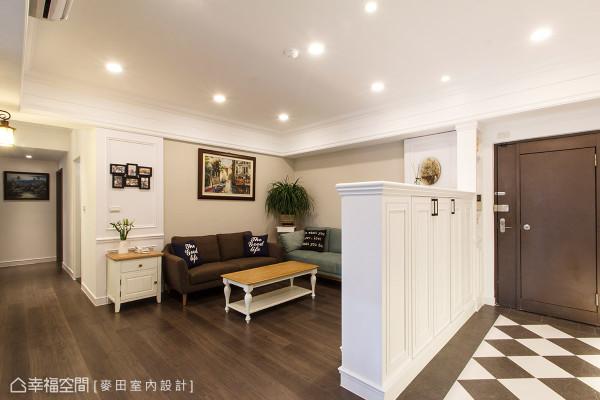 美式风格的白色柜体,除作为玄关区的鞋柜使用外,亦为厅区的电视背墙。