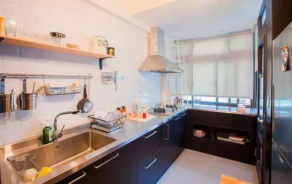 纯黑色L形橱柜与不锈钢台面让厨房看起来利落干净,墙面上的搁架设计也让这间厨房发挥了很大的作收纳用。