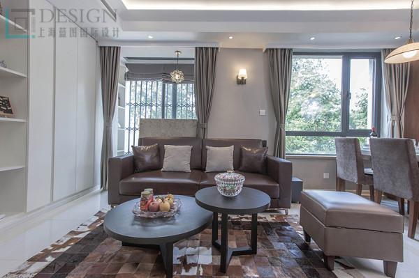 客厅的茶几款式新颖,吊顶简约的处理,利用暖色系的灯带展示的更加温馨。