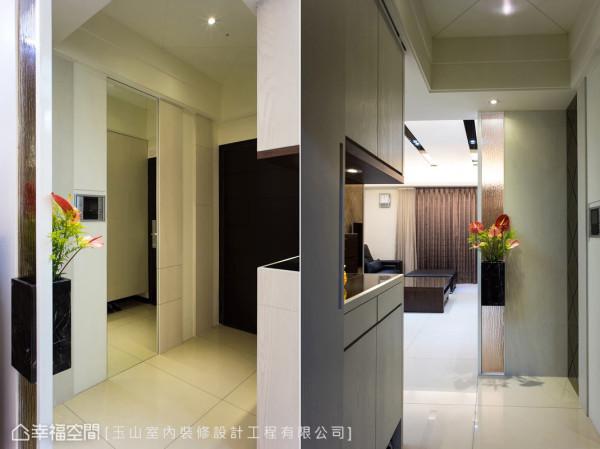 入门后,玄关屏风以带有穿透感的压花玻璃作为屏隔,左侧的柜体则设置挖空台面,可以放置钥匙等生活小物。