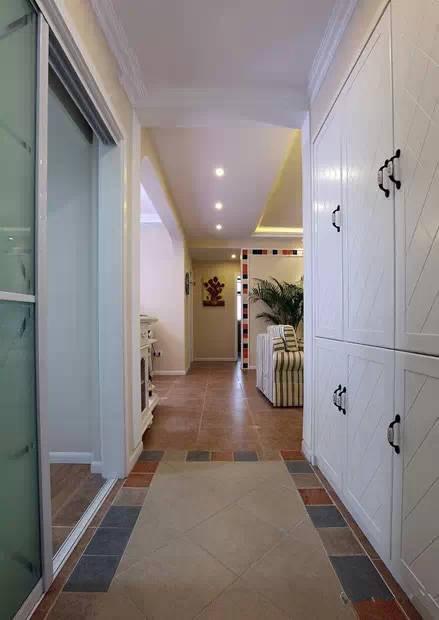进门处地砖的斜纹和柜子上的纹理非常搭,正对着的玄关处挂着的是一幅向日葵装饰画。