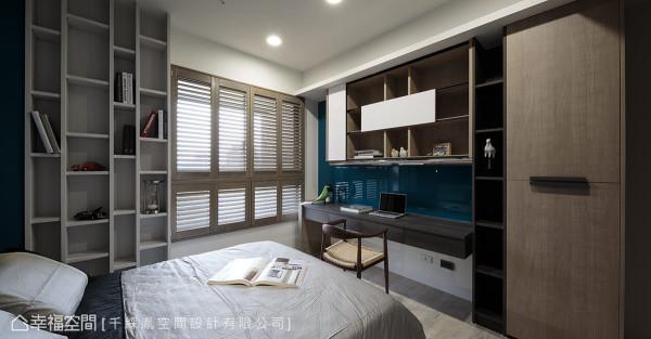 呼应蓝色系床头主墙,书桌墙面亦采相同色系烤漆玻璃与之搭配。