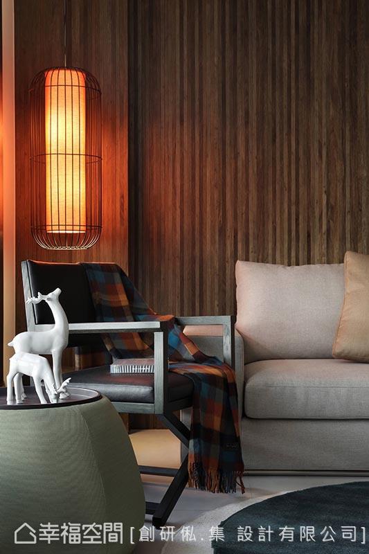 在带有浓郁木质纹理的沙发背墙前,一盏仿旧的设计款吊灯晕染了空间的禅意宁静。