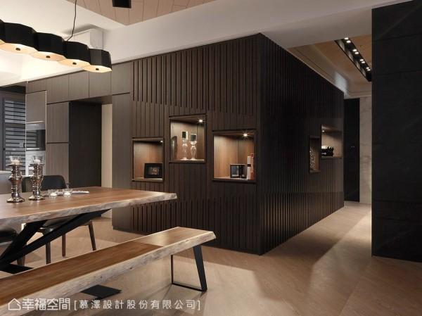 深色木作隔墙兼具展示功能,渐进有序的格栅线条带出空间的立体层次;面向廊道的立面则隐藏有通往起居工作室的动线。