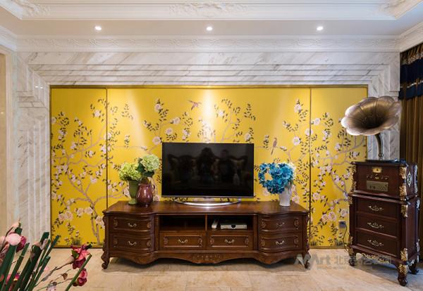 客厅空间通过变化的石材边框与真丝硬包的结合首先解决了该墙体通往卧室的门的问题,同时让整个墙面空间的比例更均衡。