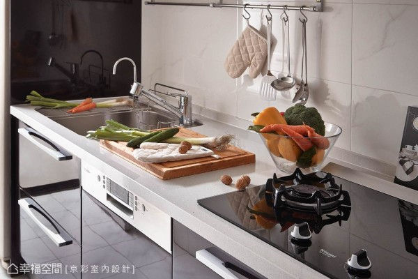 回应空间黑白的时尚色调设定,厨房以容易清洁的镜面材质重新规划入充裕的煮食机能。