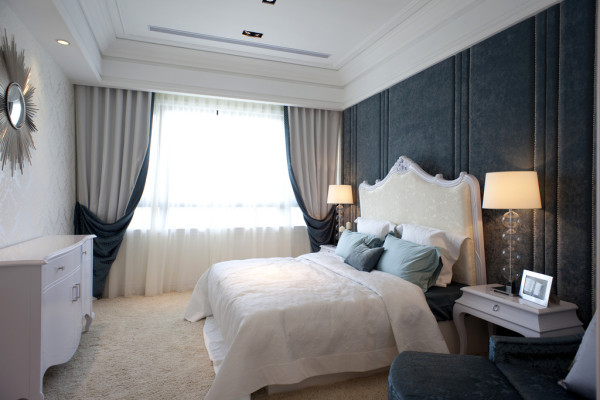 主卧室依旧白色为主色调,背景墙采用蓝色造型软包与镜面的结合使得空间的层次感更加鲜明