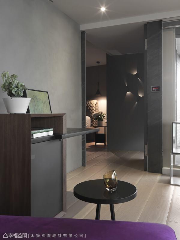 铁灰色薄片板岩的连续纹理,可将通往主卧的门片细腻藏起,平日门片开启时,主卧入门处的灯艺造型形成视觉端点。