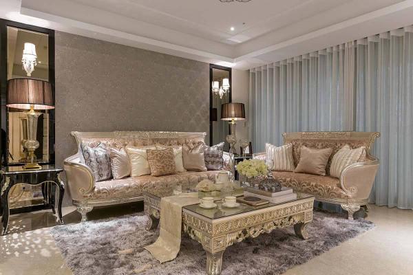 沙发背墙采用古典图腾壁纸与对称茶镜,烘托前方饰以金漆的古典家具。