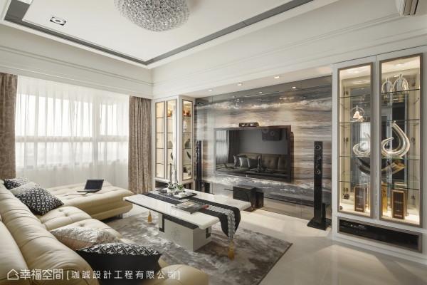 客厅选择横向纹理的蔚蓝海岸大理石,上下段落与柜内也使用灰镜延伸,达到放大之效。