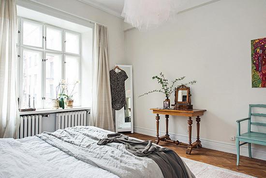 卧室里秉持了同样简洁的布置,淡雅的色彩带来了温和舒适的睡眠空间。房间里的吊灯十分引人注目,灯罩的层层纱幔营造出浪漫梦幻的氛围。