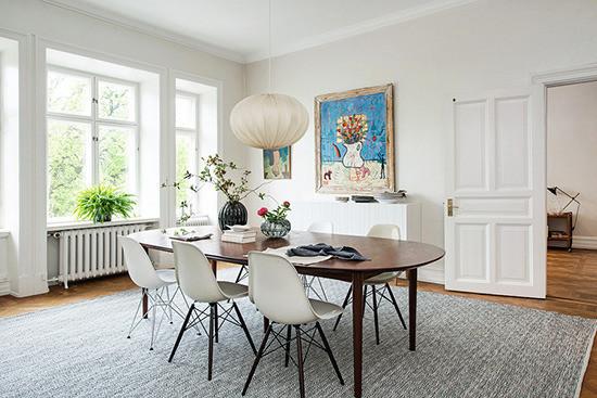 餐厅空间同样敞亮,一张大餐桌可供多人同时就餐,餐桌和餐椅的款式同样简单而不浮华,球形吊灯温馨而充满个性。墙上的空白处,仍然由艺术画作来填满。