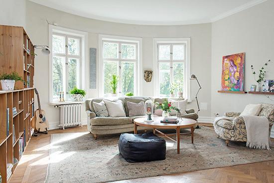 宽敞的客厅稍带一点弧形,显得更加优雅,三扇窗户透进明媚的阳光。灰色的沙发倚窗而坐,前面是一把让人倍感亲切的圆形茶几。墙上的装饰画,让空间平添几分艺术色彩。