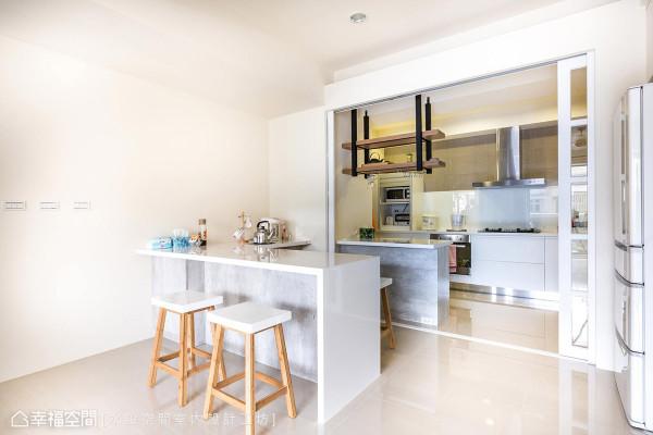 简约色调成为烹饪与用餐空间的风格写照,仅隔一道玻璃拉门划分厨房与餐桌空间。
