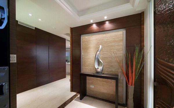 迎向大门的玄关,由电视墙面衍伸出来,不仅放大后头客厅空间的电视墙格局,也顺势利用为玄关空间,以石材的质感来设定端景,呈现进入开放大户的心情转折。