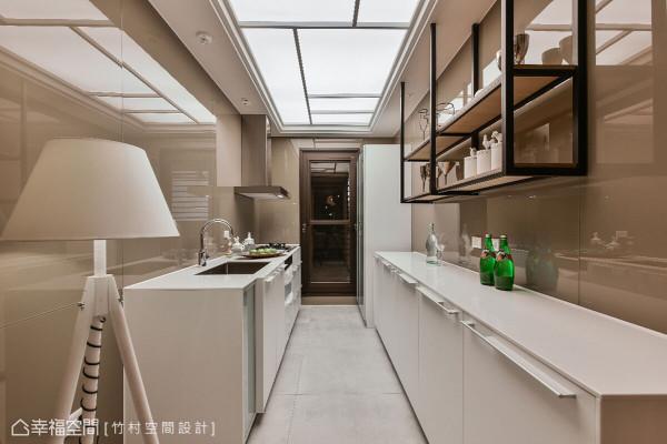 使用悬吊式橱柜和悬浮式厨具,加上天花板如天井般的灯盒设计,藉此营造出放大的视觉效果。