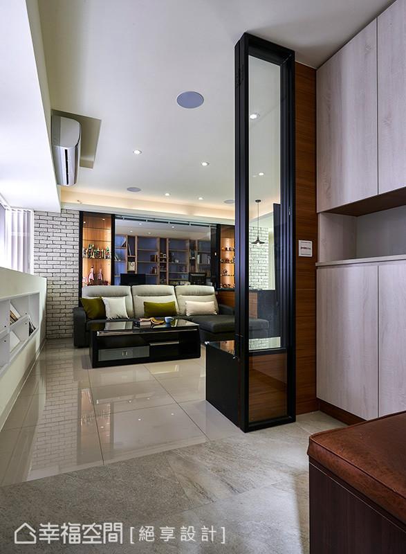 以板岩砖为地坪,自然划分玄关与客厅领域;黑色铁件的折迭门扇让空间同时保有开放与分界。