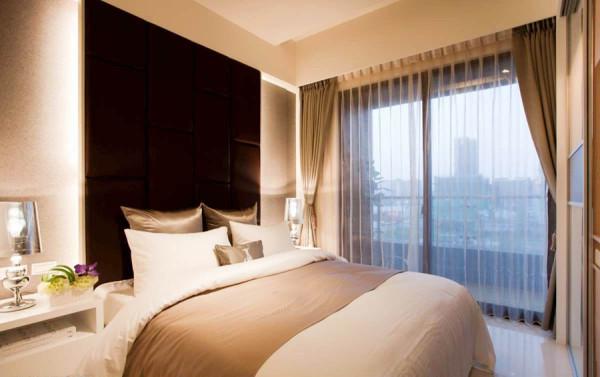 干净立面上搭配深色绷布主墙,加上后方光源的烘托,突出主卧气势。