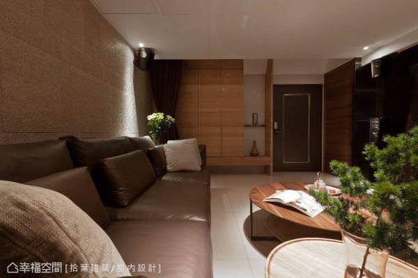 玄关旁,特别以木纹打造出收纳空间,利用层板隔出风格展示区。