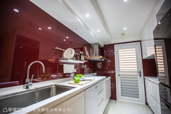 为了搭配屋主购置的酒红色冰箱,厨房壁面运用酒红色玻璃烤漆,清亮的设计带来一致性的视觉效果。