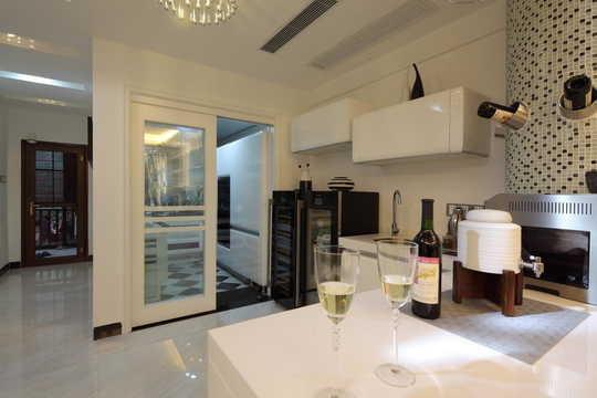 在整体白色的氛围中,黑色的橱柜作为元素的点缀,巧妙的利用吧台一边的柱子,用夹板造型做出了半弧形的倒插红酒的酒架。如此独特。黑白的马赛克装饰与客厅的书吧整体上就协调起来,如此呼应。
