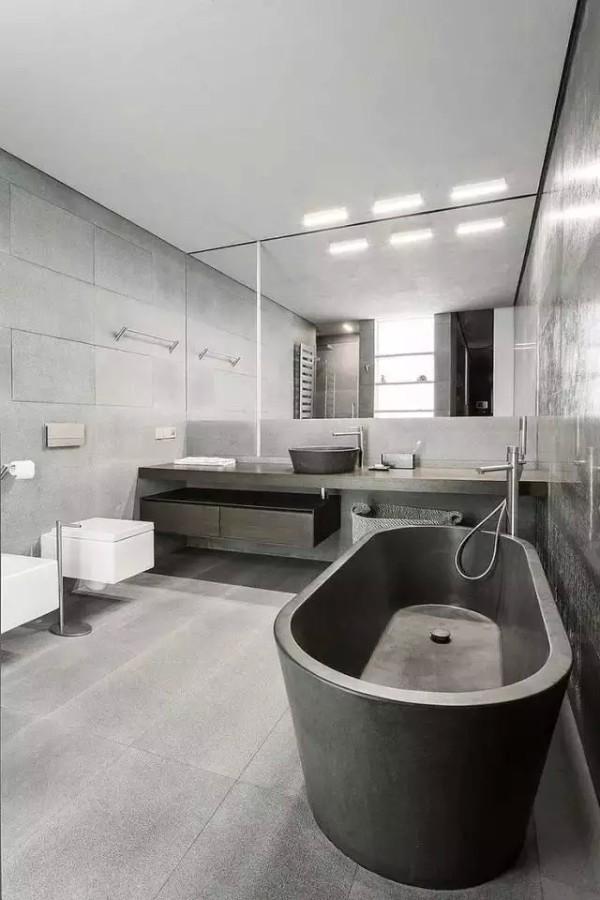 狭长型卫浴间设计,灰色主打很简洁。浅灰色的木洗手台面与浴缸的灰色遥相呼应,另一边的白色系来进行点缀。