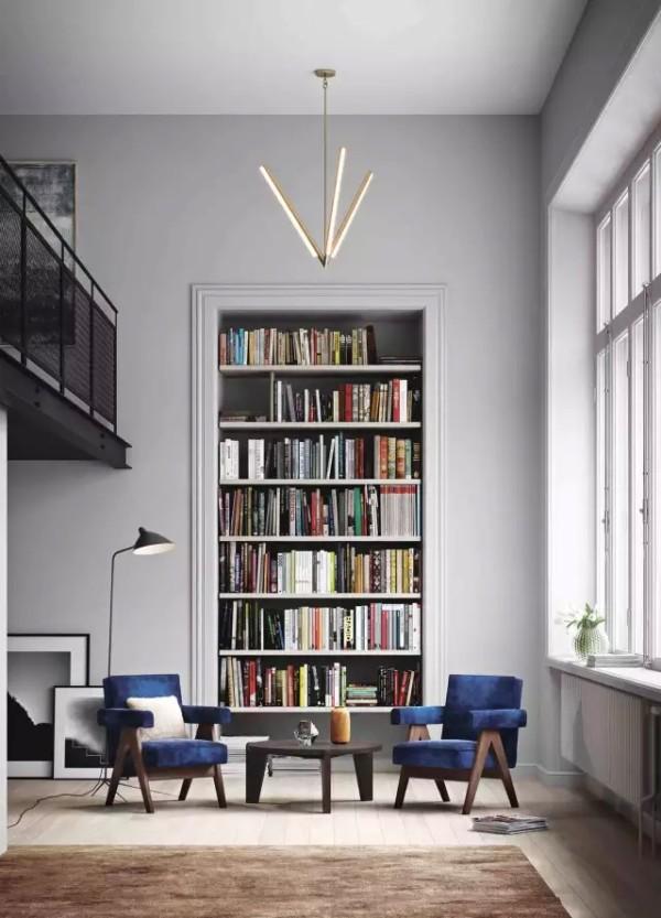 ▲书房内的跃层书柜与墙壁融为一体,即节约空间,又成为一种装饰,搭配具有线条感的吊灯和两把宝蓝色扶手椅,美感十足。