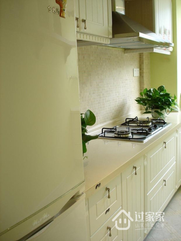 厨房清一色柔和色调,象牙白的橱柜配上几盆翠绿的植物,极具亲和力,使人感到煮饭做菜还是一件悠闲自得的事情