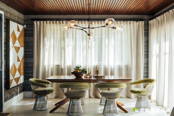 房间里的各个区域是连贯的,里面有一个开放的厨房以及就坐休息区。暗黑色的酒吧凳为人们提供了更多一种座位选择,并且和木制的欧式橱柜遥相呼应。