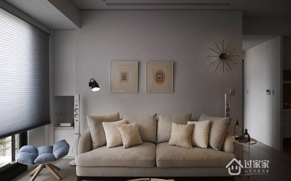 暖灰色调的沙发背墙缀饰风格掛画、造型时鐘与阅读灯,简约中可见设计品味。