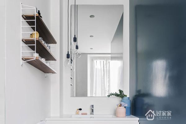洗手间与淋浴间相互对应,那抹鲜活的深蓝色墙面延伸到洗手间。安放一些隔板来存储物品,搭配爱迪生的灯泡简约细致。