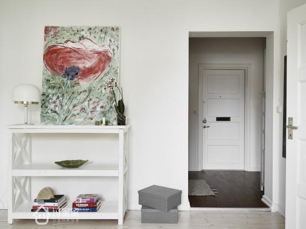 玄关处摆放了与客厅同系列的挂画,白色家具简单实用。