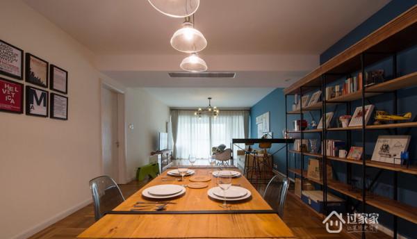 餐桌采用木质的桌面与旁边的框架式书架及地面和板材形成良好的呼应作用,一个简单实用的吧台把客厅与餐厅合理的分割开来。