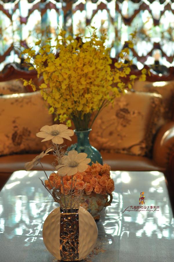 茶几摆放着一个蓝色的瓷花瓶,花瓶里明黄色的插花柔美地盛开,与周围的幽雅环境搭配得十分和谐。