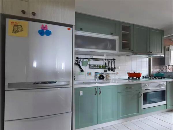 开放式的厨房用小白砖铺贴,定制的橱柜也是湖蓝色的门板。