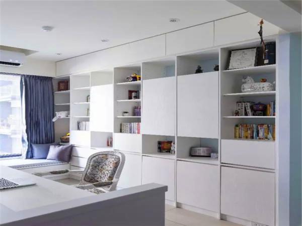 书房背景同时也作为客厅背景是一整面的收纳柜墙,用大小交错的门板和开放隔层来丰富视觉层次。