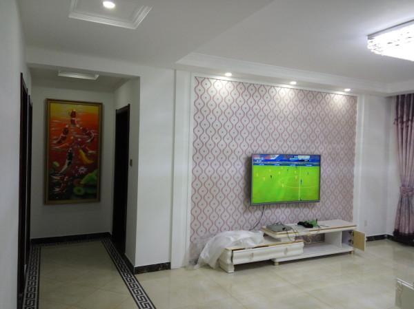 电视背景墙采用石膏板做的几何造型,既简单又大方,再加上线条形的壁纸(属暖色调),配上顶部照下来的灯光,整个电视背景墙把客厅提升起来。沙发背景墙只做了简单的处理,上面可以放装饰画等。