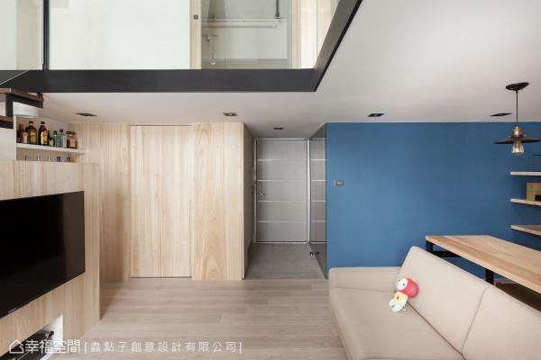 入门后,左侧由钢刷木皮铺设的立面,作为鞋柜与储藏室使用,右侧蓝色漆面后方则藏有卫浴空间。
