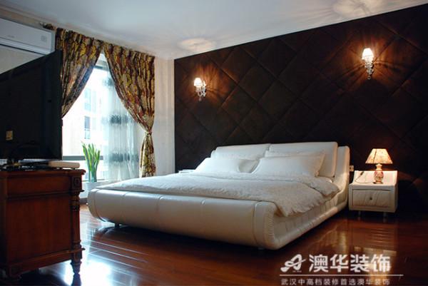 深咖色背景软包搭配原木地板,佐以灯光效果渲染,暖色系的布景让业主一回家就能切身感受到真实的温暖。米色床品及柜体打破单一色系的乏味,将卧室简约而不简单的品质感表现的淋漓尽致。