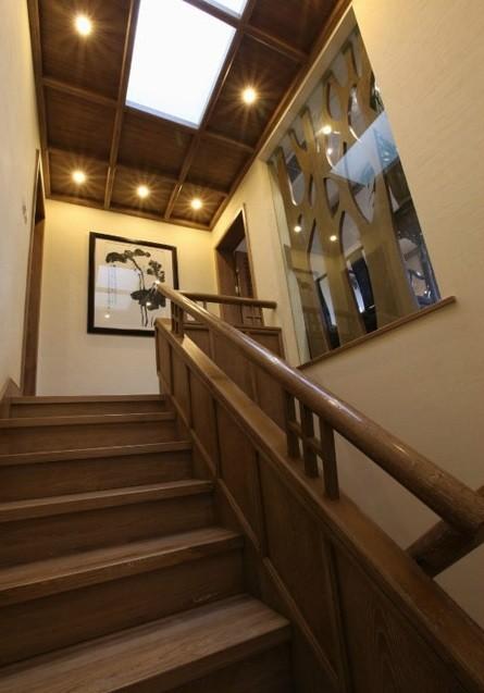 复式家居中总少不了连接上下层的楼梯,这个朴素的木质楼梯设计,虽没有复杂的点缀和装饰,却有着颇具古典韵味的典型气质。吊顶上的射灯按照一定的形状排列布置,营造出幽远意境。墙上的水墨画让空间有了艺术气息。