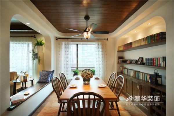 客餐厅墙面打通做圆拱形吧台,为半开放式空间塑造出景中窗的视觉效果,在自然光线的作用下,更显明亮悦目。与之相呼应的是,餐桌一侧的边柜为半内凿式整体收纳墙,将书籍和家居饰品进行完美地收纳和展示。